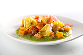 Tortelloni with Fossa cheese filling on a cream pea soup with pumpkin and thin strips of salame felino